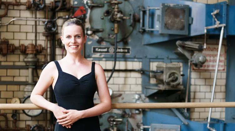 Annelie Plock, junge Frau, stehend vor Ballettstange, Arme dort aufgestützt, Blick lächelnd in die Kamera, Dutt