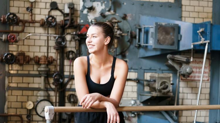 Celina Geigle, Frau, jung, Arm verschränkt lehnend auf Ballettstange, Blick lächelnd nach links