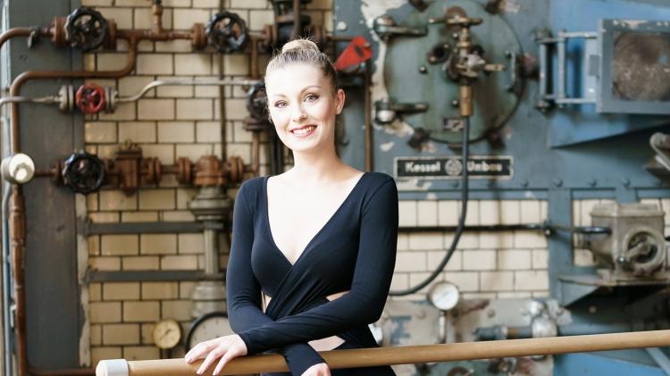 Franziska Frey, Arme verschränkt auf Ballettstange, junge blonde Frau, schwarzer Body, lächelnd