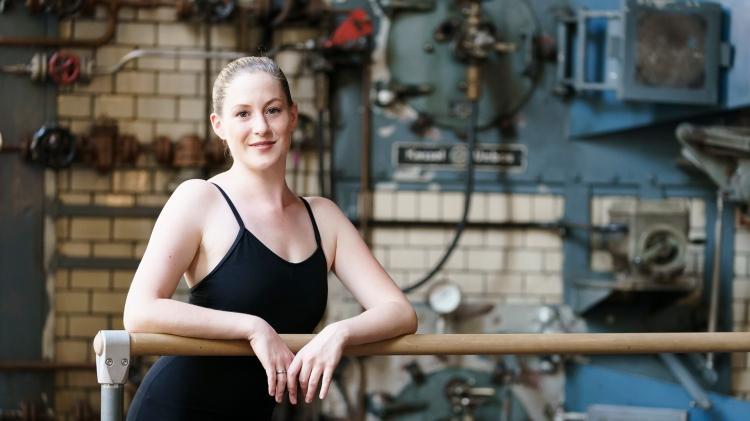 Lisa Eldner, junge Frau, schwarzer body, Arme aufgestützt auf Ballettstange,